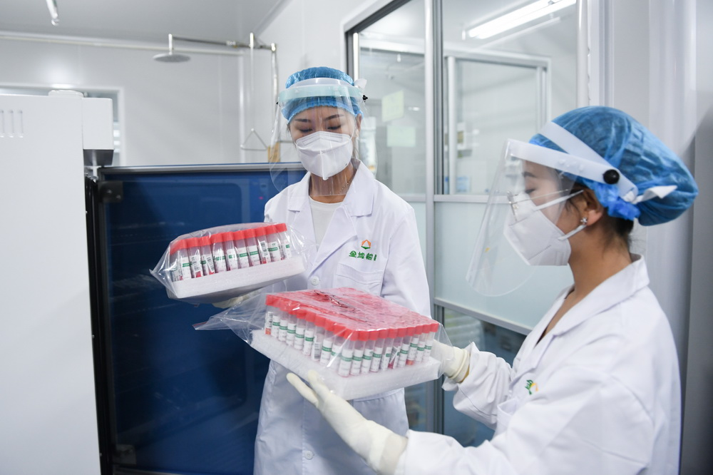 检验人员将灭活的样本从设备中取出(6月25日摄)。